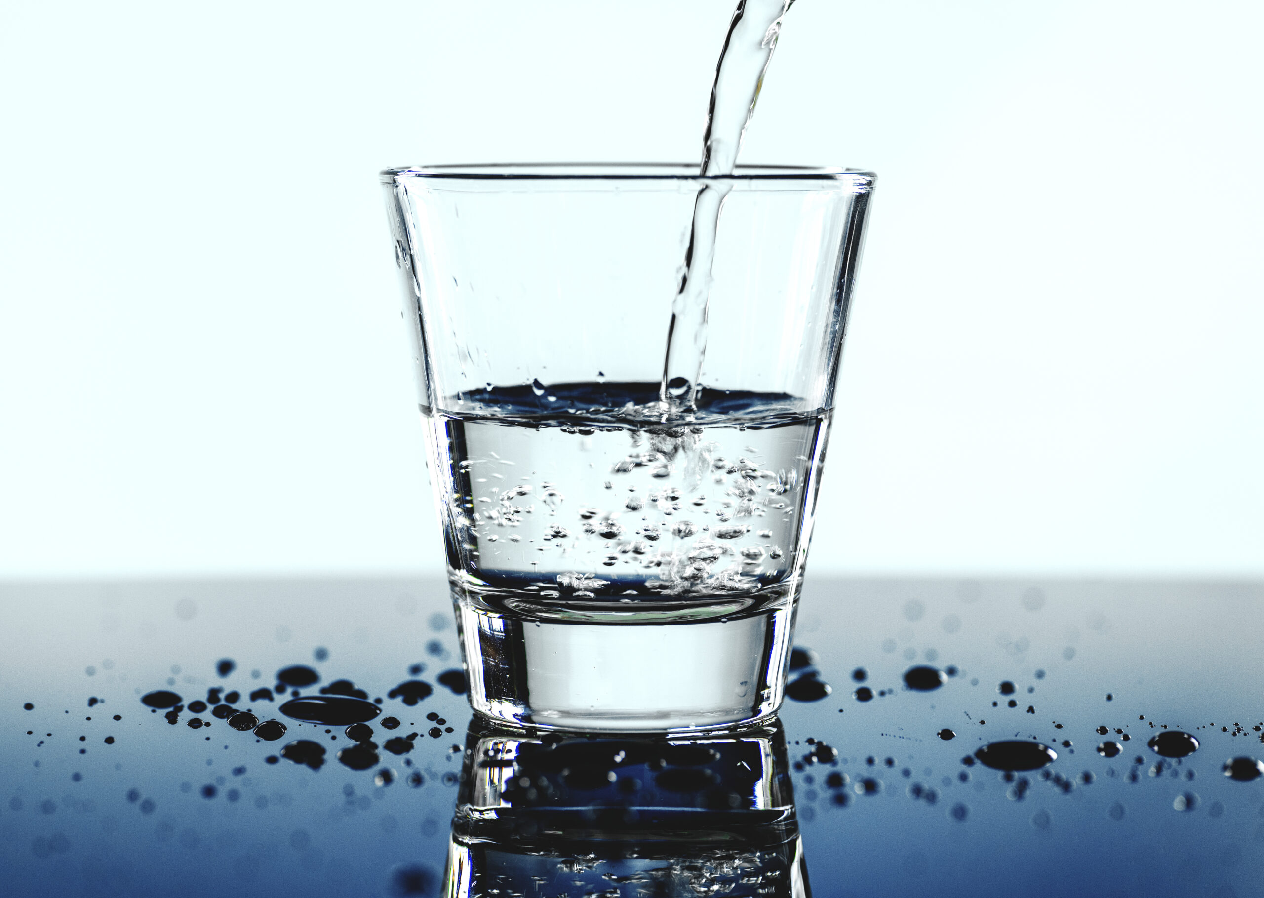 a glass of water with blue background