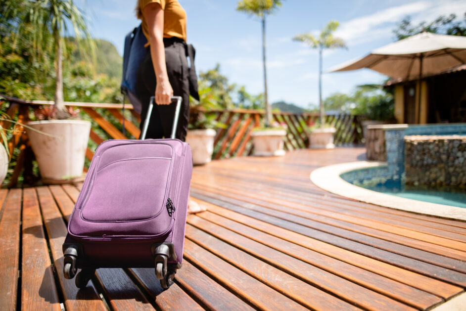 woman with suitcase at a tropical resort for her vacation