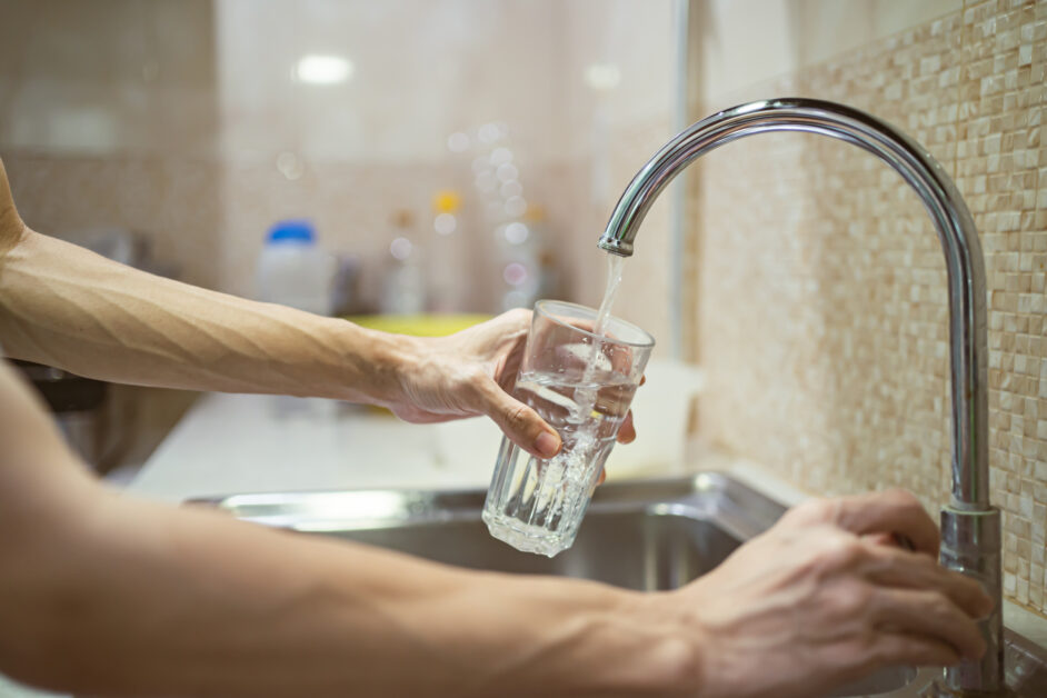 person filling a glass with tap water