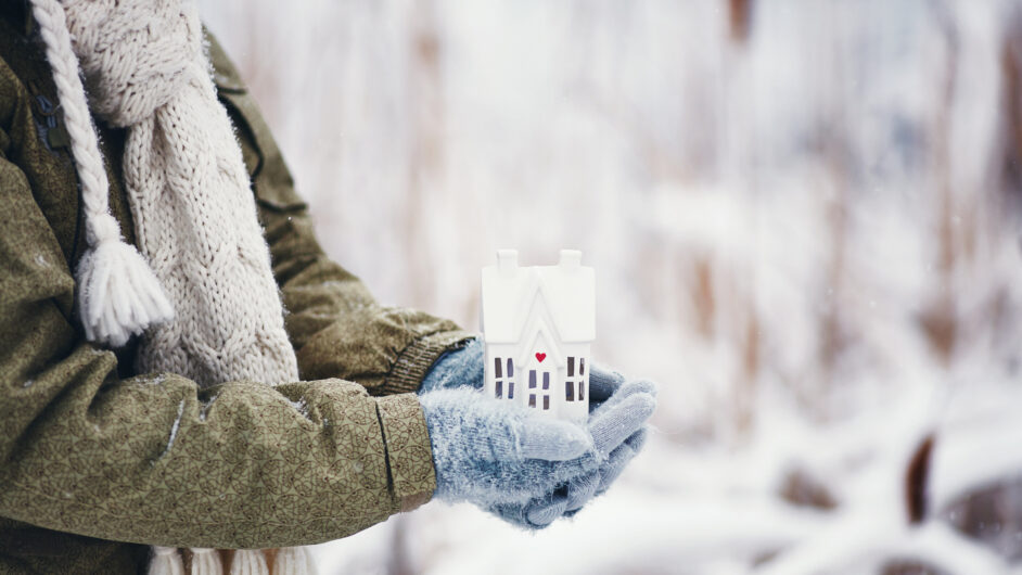 hands holding tiny home in snowy weather